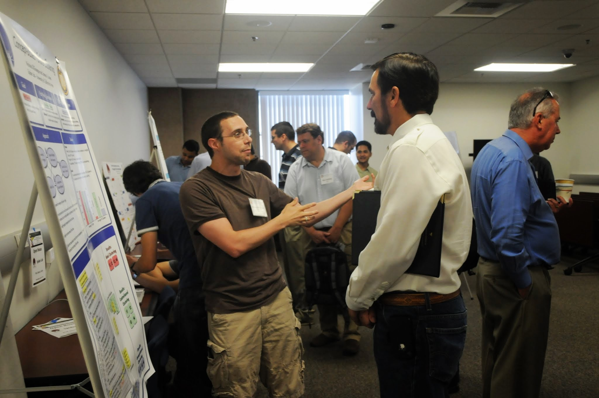 Ph.D. student Nicholas DiGiuseppe presents poster to industry attendees at Forum Open House.