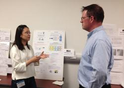 Ph.D. student Di Yang explains her work to Dr. Lee Eric Dashofy, The Aerospace Corp. at Open House.