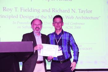Taylor accepts Impact Paper award from SIGSOFT Chair Prof. Medvidović.